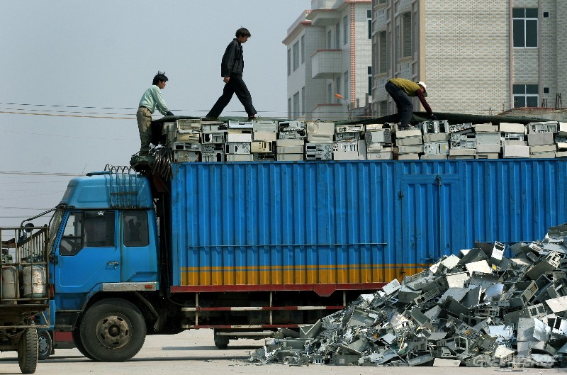 Workers unpack a truck-load of e-waste which has just arrived for processing in Guiyu in Guangzhou province. (© Greenpeace/Natalie Behring)