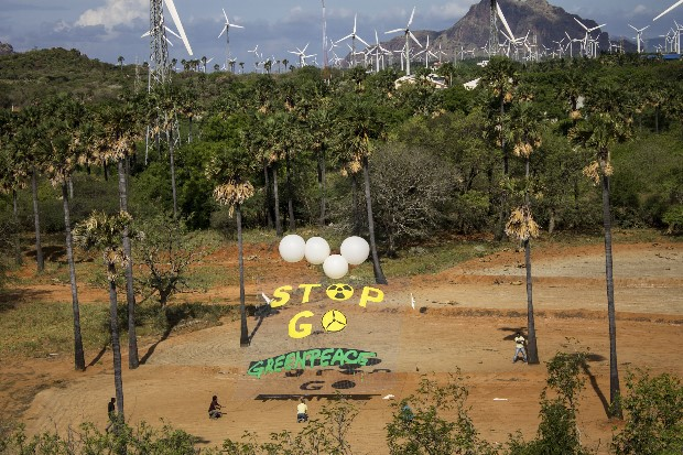 Greenpeace activists hold a banner in the Nagercoil wind farms