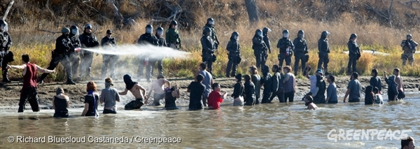 Water Protectors engineered a makeshift wooden pedestrian bridge over the Cantapeta Creek. They were trying to access ancestral burial grounds they believe are being damaged by the Dakota Access Pipeline construction. Heavily armed law enforcement officials were deployed. As they pulled the bridge apart with boats, the Water Protectors swam and used their own boats to cross the water. Standing unarmed in the cold water, the protectors were forcibly repelled by the enforcers with tear gas, pepper spray and rubber bullets. Standoffs between the Water Protectors and law enforcement over the Dakota Access Pipeline continue in the area that has become ground zero for opposition to a $3.7 billion project that would move domestic crude oil across four states and destroy tribal lands.