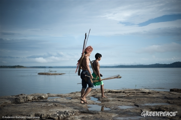 Two Munduruku boys walk along a river while holding spears. The Munduruku people have inhabited the Sawré Muybu in the heart of the Amazon, for generations. The Brazilian government plans to build a series of dams in the Tapajos River basin, which would severely threaten their way of life.
