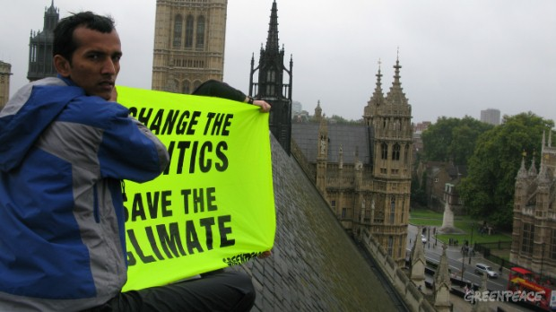 "Brikesh Singh, climate campaigner, Greenpeace India, unfurls a huge banner on the roof of the Palace of Westminster's Great Hall that says: ""CHANGE THE POLITICS, SAVE THE CLIMATE."" 
