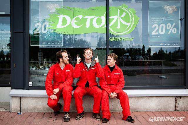 Greenpeace activists smiling up at their work - Helsinki Adidas Outlet Store - rebranded!