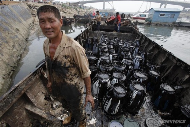 Fleet of fishermen help to clean up Dalian oil spill.