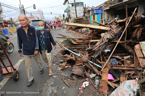 An elderly couple walk past rubble left by the damage caused by Typhoon Haiyan in Tacloban City.