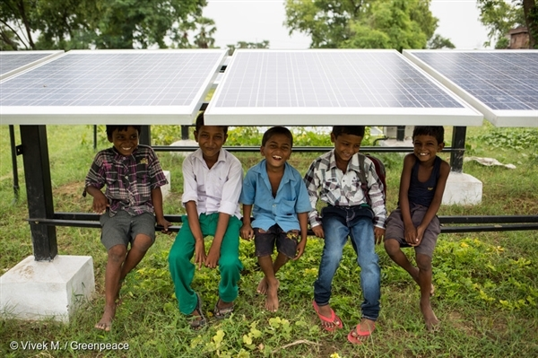 Children sit under solar panels at Bishunpur Tolla, Dharnai village. A solar-powered micro-grid is now supplying electricity to the village.