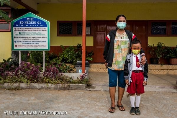 A mother and her child stand in front of the school building that is currently closed due to haze caused by forest fires in Benua Kayong, Ketapang district, West Kalimantan province. 21 Sep, 2015