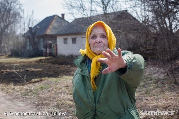 A woman stands by a burnt house in Stary Vyshkov village. 08/04/2016 © Greenpeace / Liza Udilova