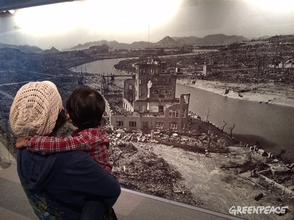 Mother and child looking at the picture of Hiroshima after the atomic bombing in the Peace Memorial Museum. ©Greenpeace