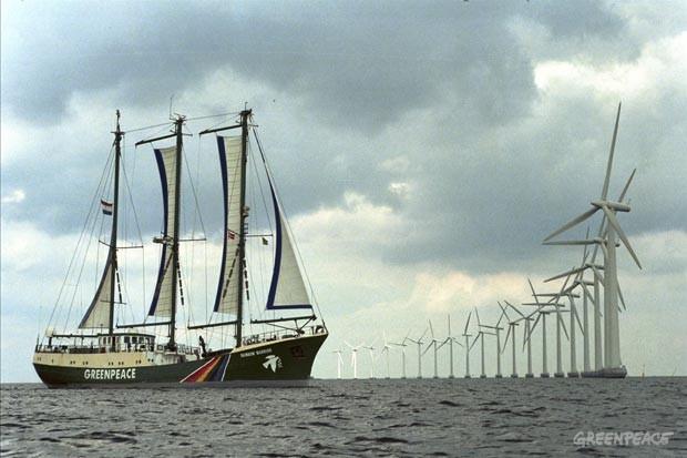 """El buque insignia de Greenpeace, Rainbow Warrior al inicio de la campaña """"Elige la energía positiva"""", tour en el Mar del Norte, Dinamarca. A la derecha, una fila de molinos de vientos en el Parque Middelgrund cerca de Copenhague."""
