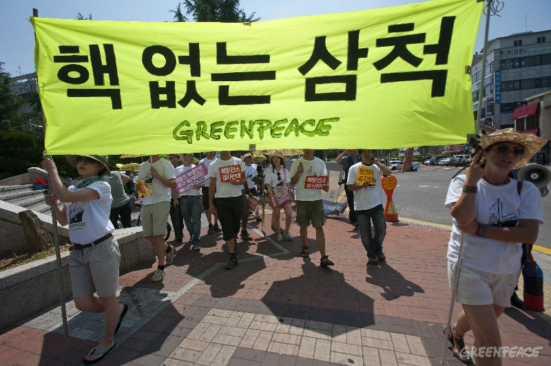 "Greenpeace activists and crew members of the Rainbow Warrior march against nuclear energy with banners bearing the message ""Nuclear Free Korea, Nuclear Free Samcheok"". Samcheok, 21 June 2011. Republic of Korea. Korea's nuclear expansion has drawn protest from local residents concerned about the safety of nuclear energy in the light of the disaster in Fukushima, Japan."
