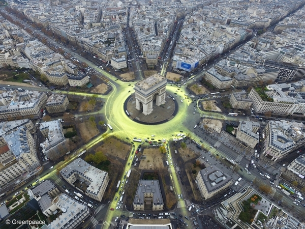 In 2015 at COP21 in Paris, Greenpeace activists create a solar symbol around the world-famous Arc de Triomphe, by painting the roads yellow with a non-polluting water-based paint to reveal the image of a huge shining sun.