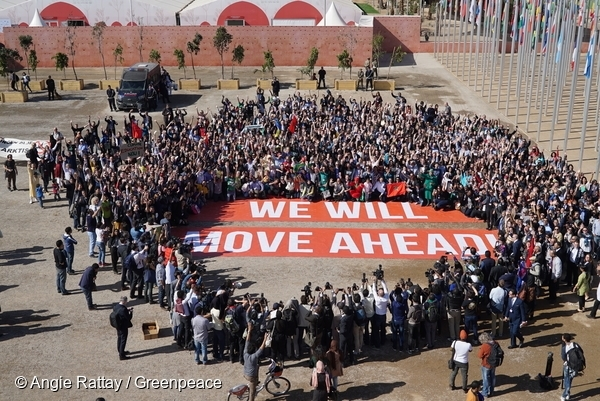 Hundreds of government and civil society supporters of the Paris Agreement pose together at the COP22 in Marrakech with a giant banner bearing the words 'We Will Move Ahead' to show their determination to move ahead with action against climate change. 18 Nov, 2016  © Angie Rattay / Greenpeace