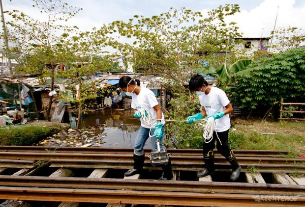 Water patrol volunteers collect water samples in Taguig City, Southern Manila