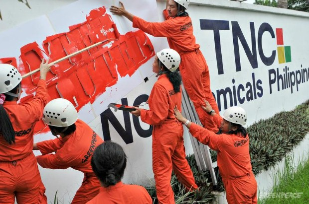 Greenpeace activists label an outer wall of TNC Chemicals Philippines Inc. with the words 'Water Polluter'