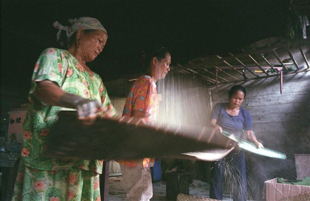 Dayak women separating rice from husks