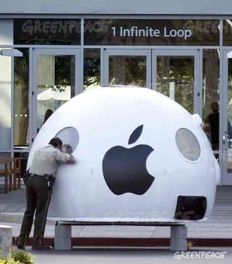 "A police officer peers into Greenpeace's ""iPod"" as part of a protest at Apple's Cupertino headquarters a few days before Apple's new renewable energy announcement"
