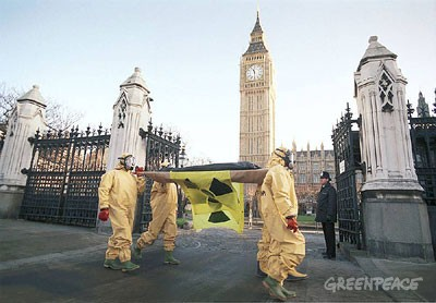 Gulf War Action.  Four Greenpeace protesters wearing radiation suits deliver a body bag on a stretcher to the House of Commons to draw attention to the risk created by the build up of nuclear weapons in the Gulf region.