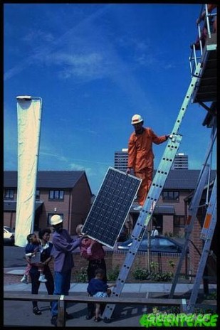 Greenpeace activists install solar panels on houses in Docklands, London.