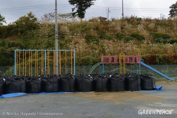 Bags of contaminated soil, mud and grass at a playground of an elementary school in Iitate village. 10/27/2014 © Noriko Hayashi / Greenpeace
