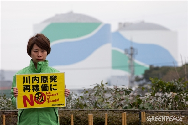 Sendai Nuclear Power Plant in Japan. Greenpeace activist holds a protest sign in front of the station. 25 Feb, 2015 © Masaya Noda / Greenpeace