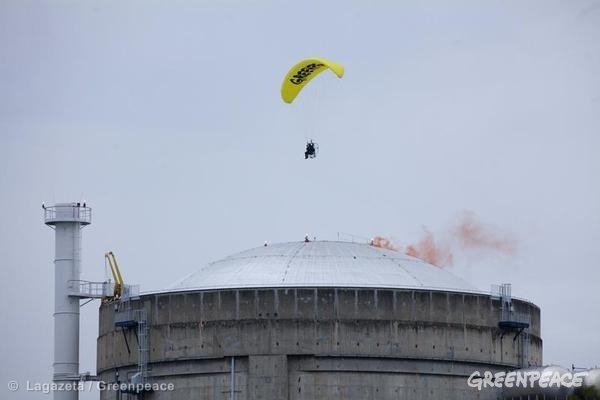 A Greenpeace paraglider flies over the Le Bugey nuclear power plant and drops a smoke device upon one reactor dome. The activist later landed inside the site. The activity highlights the vulnerability of French nuclear power.