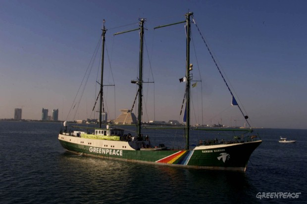 Rainbow Warrior sails into Doha to challenge the WTO to force the US to commit to the Kyoto Protocol on climate change.