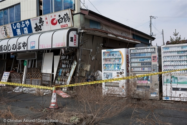 An abandoned convenience store in Namie and Japan's famed vending machines with sake and other products, blocked off by tape.