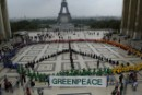 Greenpeace creates a symbol of peace in the shadow of the Eiffel Tower to commemorate victims of terrorism