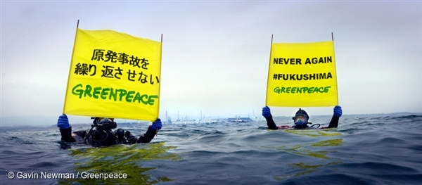 Greenpeace divers hold up banners at Fukushima Daiichi nuclear plant