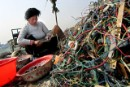 A migrant worker strips plastic from wires