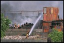 Fireman fighting fire at PVC storage warehouse