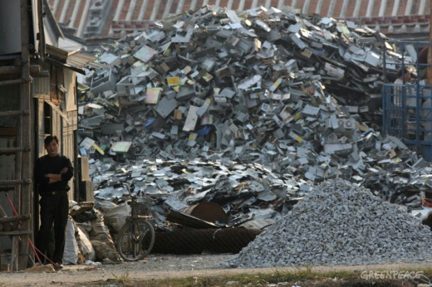 Owner of an e-waste scrapping yard stands in front of a mountainous pile of computer waste waiting to be scrapped to recover useful plastics and metals.
