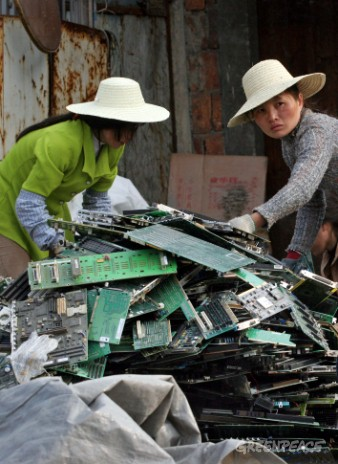 Chinese women dismantle computer circuit boards in an e-waste scrap yard. After sorting the circuit boards they will be burned over open fires to extract metals. The smelting releases large amounts of poisonous gases.