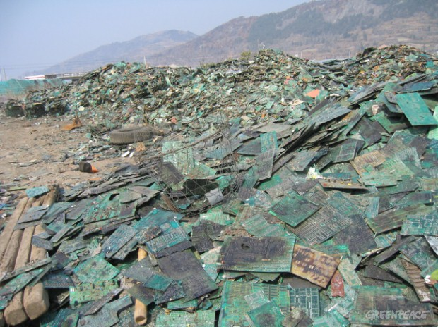 Piles of circuit boards from hazardous computer waste stretch into the distance near an e-waste scrap yard. The circuit boards will be smelted by hand to extract metals. Smelting releases highly poisonous gases and pollutes the environment.