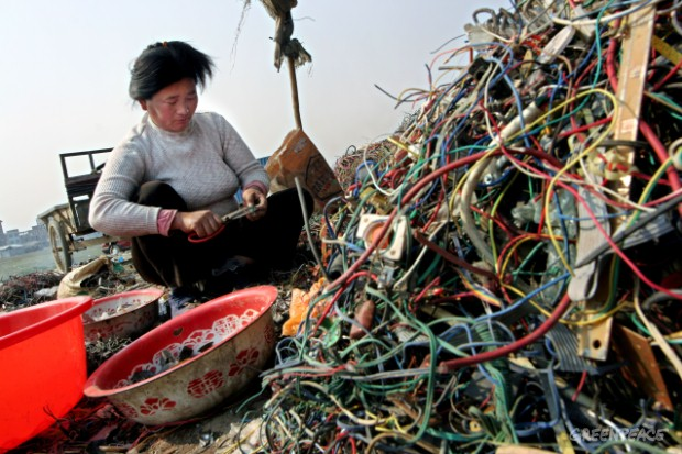 A migrant worker strips plastic from wires to extract useful metals. The plastic on the wires is often PVC which contains toxic chemicals and produces large amounts of pollution when disposed, often by burning in the open air.