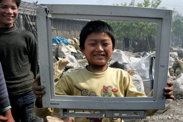 A migrant child from Henan province holds up a piece of e-waste. It was once a Nokia computer screen, now dumped in China and dismantled by poor, unprotected, migrant workers.