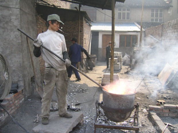Chinese man smelts computer parts in the open air to extract metals. Open air burning of computer waste releases large amounts of toxic fumes.