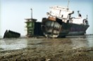 A partly scrapped hulk of a tanker lies crippled