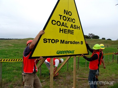 Greenpeace activists erect signs around the perimeter of Marsden B