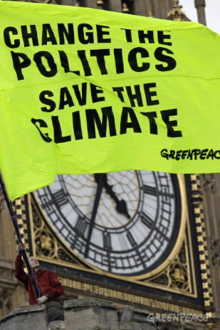 A Greenpeace UK volunteer waves a flag from above the UK Parliament that reads, 'CHANGE THE POLITICS, SAVE THE CLIMATE'. Fifty-five Greenpeace volunteers scaled the walls of the Houses of Parliament occupying the roof to call for for a new style of po...