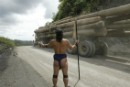 Penan man watches a timber truck
