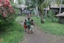 Children walking through a village in Lake