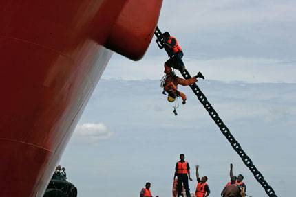 A policeman pushes a Greenpeace climber down from the anchor chain of the Gran Couva © Greenpeace/Novis