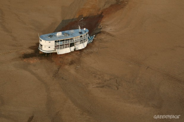 Big river boat trapped on a sand bank, during one of the worst droughts ever recorded in the Amazon. The drought is severely damaging the world's largest rainforest, with wildfires breaking out, fresh drinking water becoming scarce and polluted, groun...