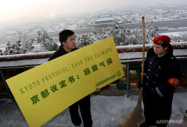 A worker looks at a Greenpeace activist holding a sign supporting the Kyoto protocol at a demonstration in a Beijing park, near the Forbidden City.