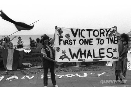Greenpeace activists holding banner that reads: 'Victory First One To The Whales', on the floor mussels read the words: 'Thank You', Brighton, UK. Demonstration outside the International Whaling Commission Meeting held in Brighton.