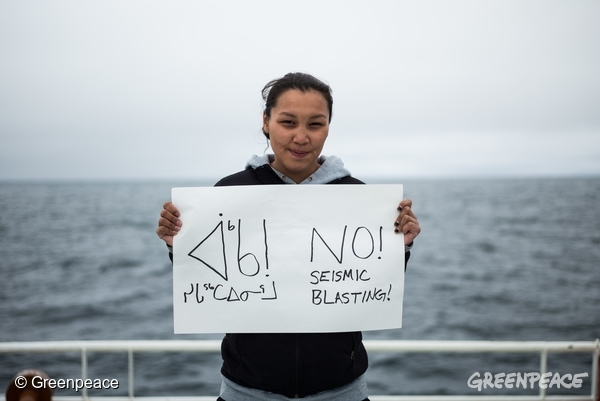Resident of Clyde River, Clara Natanine stands on the deck of the Arctic Sunrise with an anti-seismic blasting sign that she made herself. 11/08/2016 © Greenpeace