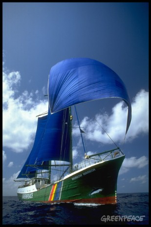 View of stern of Rainbow Warrior with blue sails out, cloudy sky in background.