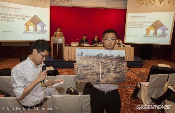 A Greenpeace activist holds up an image of creeping desertification next to a China Shenhua Energy 'Coal-to-Liquid' (CTL) plant in Ordos, Inner Mongolia, at the company's interim results conference. The CTL process is a controversial method of converting coal to various forms of oils and plastics, and is highly water intensive. Greenpeace accuses the company of depleting the water table, poisoning wells and hastening desertification in and around Ordos. Thousands of traditional farmers in and around the Inner Mongolian village of Haolebaoji, where the CTL plant is exactly located, have lost their livelihoods, as their crops have dried up and their livestock have died - all due to lack of water. Greenpeace is calling for an immediate suspension of the project.