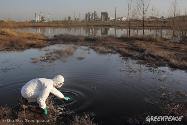 A Greenpeace investigator takes samples of waste water discharged by the Shenhua Coal-to-Liquid Project into a sand bank where it is left to seep into the ground and evaporate. For ten years, the Chinese state-run organisation Shenhua Group, has been exploiting water resources at a shocking scale from the Ordos grasslands to use in its coal-to-liquid project (a process for producing liquid fuel from coal) and illegally dumping toxic industrial waste water. Shenhua's operations have sparked social unrest and caused severe ecological damage including desertification, impacting farmers and herders who are facing reduced water supplies in what was once an abundant farming area.